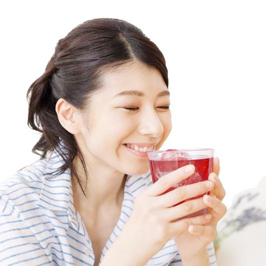 自分で選んだザクロジュースを飲む女性