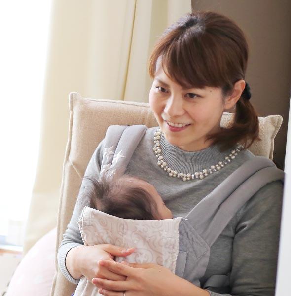 赤ちゃんを抱いてインタビューに答えています